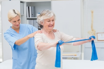 Nurse assisting senior patient in exercising with resistance band