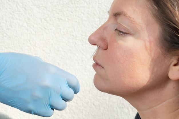 Nurse in blue gloves makes nasal corona virus test to woman