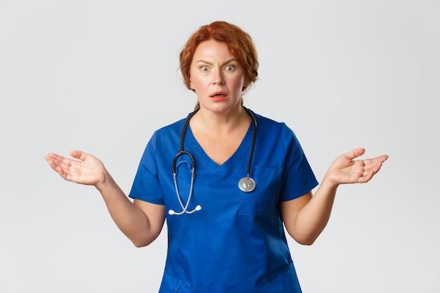 看護師は何が起こったのか理解できず、青いスクラブを着て、手を横に広げ、灰色で心配して緊張しているように見えます