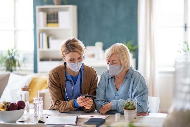 屋内で血糖値を測定する、年配の女性患者を持つ看護師、介護者、または医療従事者。