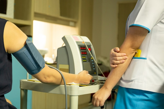 Nurse checking blood pressure on monitor screen for patient health in hospital.