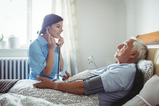 Nurse checking blood pressure of senior man