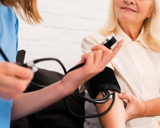 Nurse checking old woman's blood pressure