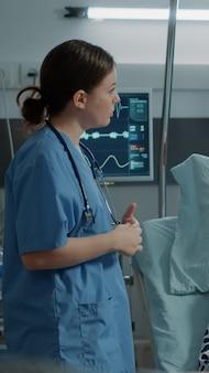병원 병동에서 아픈 환자의 산소 농도계를 확인하는 간호사