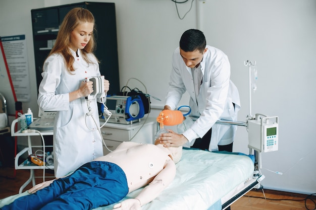 Nurse conducts resuscitation. doctor helps woman to perform the operation. students practice medicine.