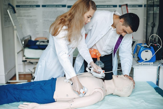 간호사가 소생술을 실시합니다. 의사는 여성이 수술을 수행하도록 도와줍니다.
