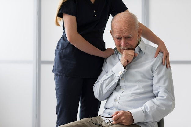 Nurse consoling old crying man