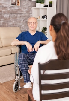 Nurse consulting an old man in wheelchair sitting in the living room.