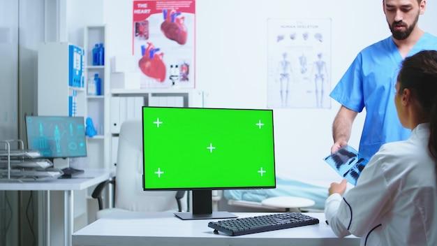 복사 공간 녹색 화면이 있는 컴퓨터에서 작업하는 동안 간호사는 병원 캐비닛에서 의사와 상담합니다. 의사가 환자 ra를 확인하는 동안 의료 클리닉에서 교체 가능한 화면이 있는 데스크탑