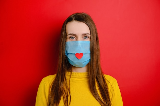 Nurse day concept. woman isolated on red background wearing a medical mask with heart on it as a way to show thank, nurses and medical staff working in hospitals during coronavirus covid-19 pandemics