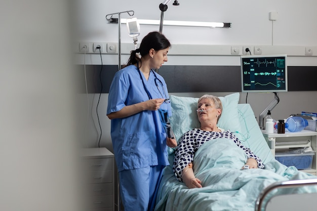 Nurse discussing with elderly patient laying in hospital bed during visit about chest x-ray