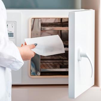 간호사는 공예품 가방에 의료용 치과 기구를 소독합니다. 병원의 위생 기계 소독. 흰색 제복을 입은 의사는 소독을 위해 소독 시스템을 청소할 때 도구 도구를 넣습니다.