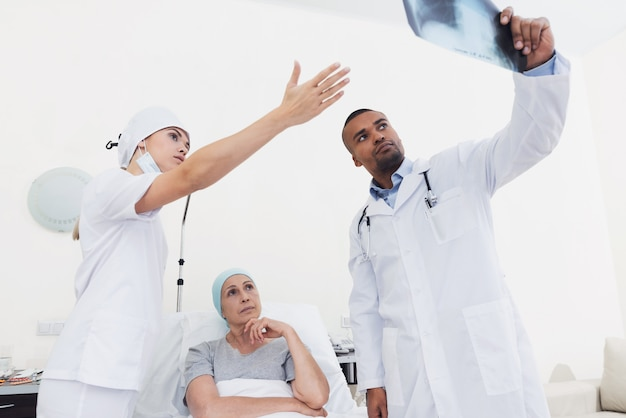 Nurse and doctor are standing next to a patient with cancer.