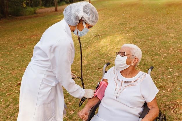 Медсестра-врач, измеряющая давление пожилой женщины