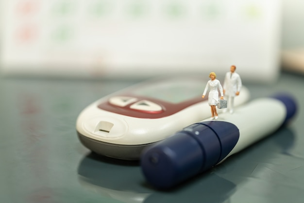 Nurse and doctor miniature figure with handbag walking on lancet with glucose meter and calender.