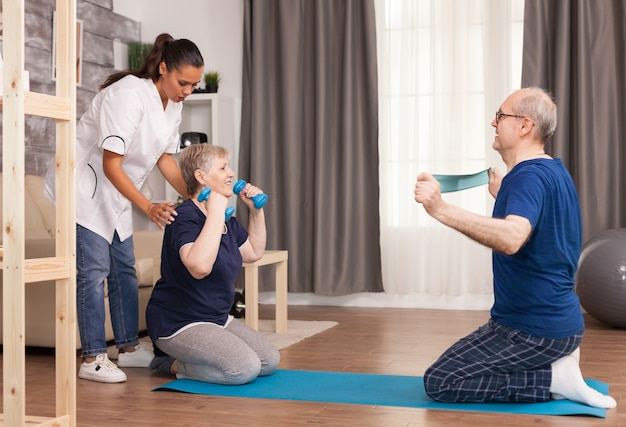 Nurse doing body therapy at home with senior couple.