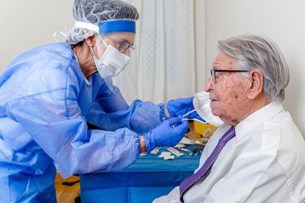 노인 마스크를 벗고 코로나 바이러스 보호를 입은 간호사