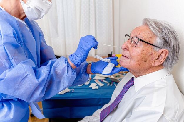 Медсестра, одетая в защитный костюм и маску от коронавируса, проводит тест на коронавирус у пожилого мужчины.