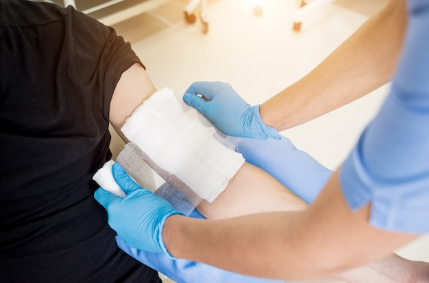 Nurse dressing wound for patient's hand with burn injury