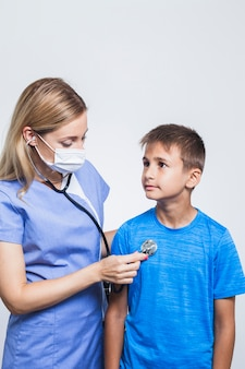 Nurse examining boy with stethoscope