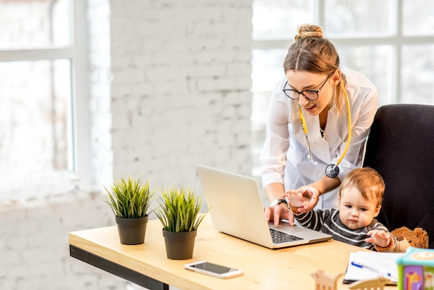Nurse examining health of a baby boy playing on the laptop in the office