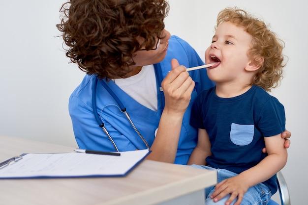 小さな男の子を調べる看護師