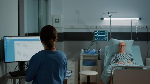 看護師が患者のためにコンピューターで医療結果を調べる