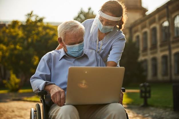 屋外の高齢者にノートの使い方を説明する看護師