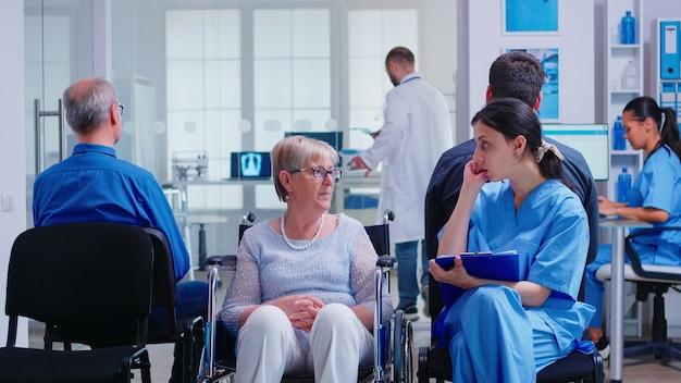 病院の待合室で障害のある年配の女性と話している間、看護師は書類を提出します。病院の受付で指示を求める患者。