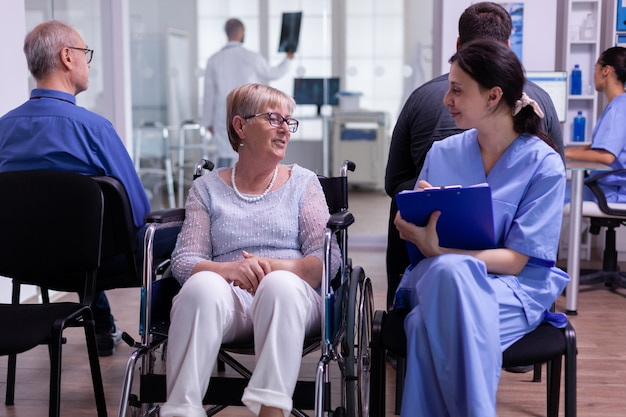 Nurse filing documents while talking with disabled senior woman sitting in wheelchair in hospital waiting area. elderly paralyzed patient explaning symptoms, assitant checking registration form