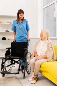 Infermiera che ottiene una sedia a rotelle per una donna anziana