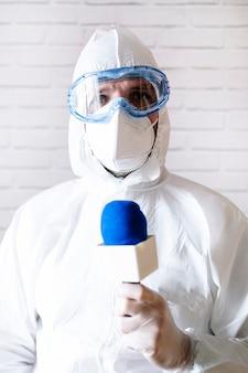 간호사는 마이크와 보호 복으로 뉴스를 제공합니다.