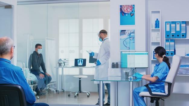 코로나바이러스에 대한 얼굴 마스크를 쓰고 의사 환자에게 방사선 사진을 제공하는 간호사. 휠체어를 탄 장애인 노인 여성을 대기실을 통해 퍼징하는 바이저가 있는 조수.