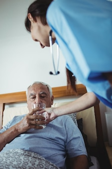 Nurse giving a glass of water to senior man