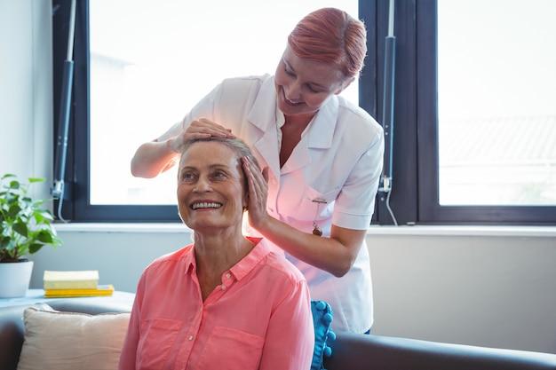 年配の女性にヘッドマッサージを与える看護師