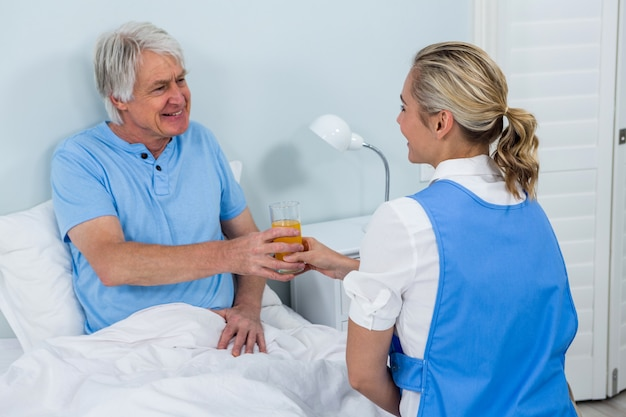Nurse giving juice to smiling senior man