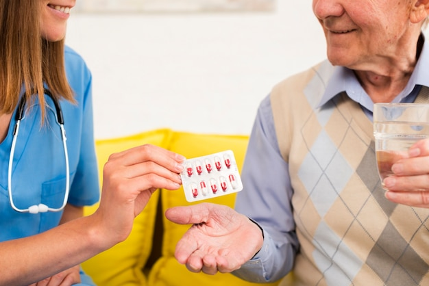 Nurse giving an old man his pills close-up