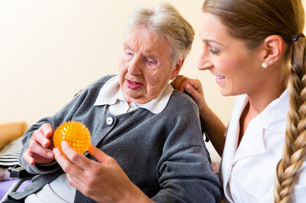 Nurse giving physical therapy to senior woman