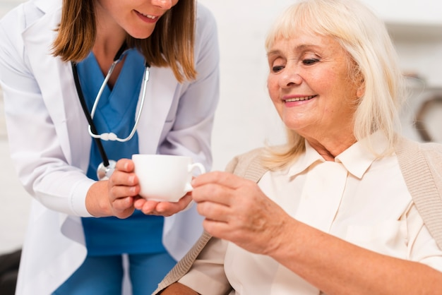 Nurse giving tea to the old woman close-up