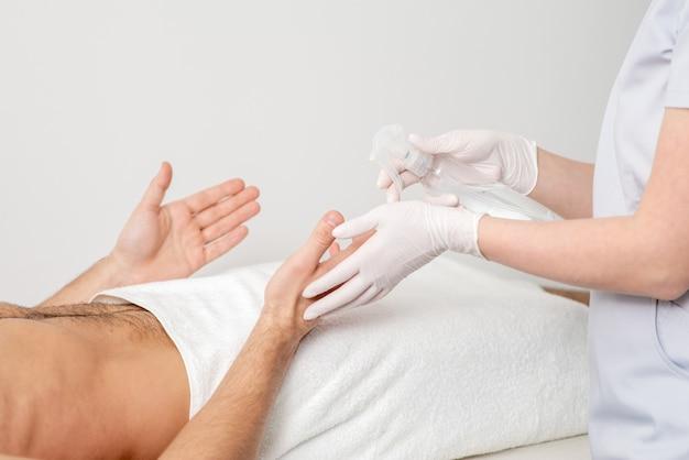 Рука медсестры, дезинфицирующая руки пациента мужского пола