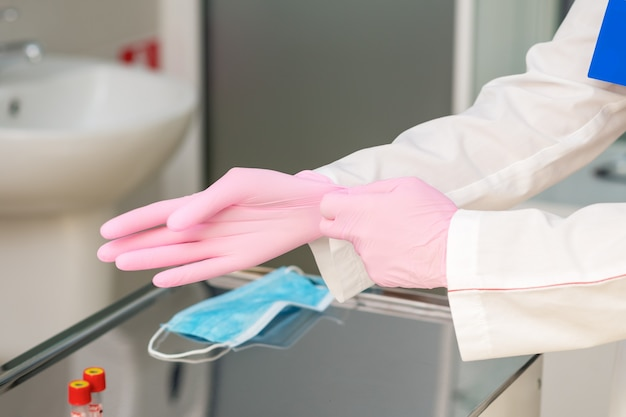 Nurse hands are putting on pink gloves in hospital, close up.