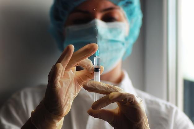 Руки медсестры держат шприц и ампулу