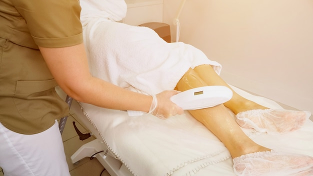 Руки медсестры в резиновых перчатках скользят по голове лазера по гелеобразной ноге в медицинском центре, производя яркие световые брызги