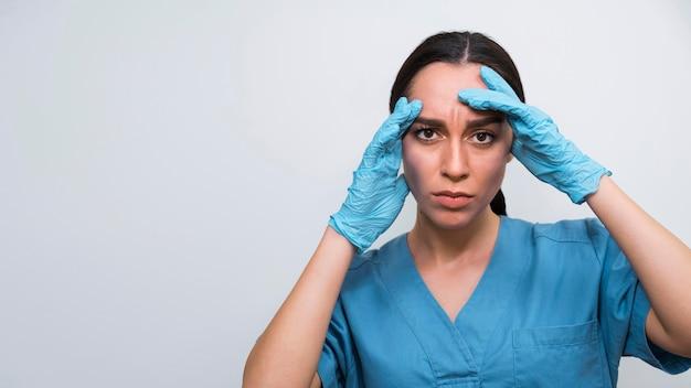 Nurse having a headache with copy space