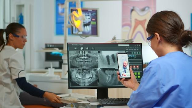 의사가 백그라운드에서 환자와 함께 일하는 동안 간호사는 전문 치과 의사와 화상 통화를 합니다. 구강 의자에 앉아 모바일 웹캠을 사용하여 치과 의사를 듣는 구강 전문의 보조