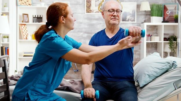 장애인 노인이 부상 후 회복하도록 돕는 간호사. 남자는 은퇴 가정의 병원 침대에 누워