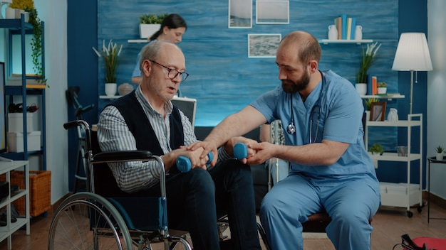 Nurse helping disabled man to exercise with dumbbells