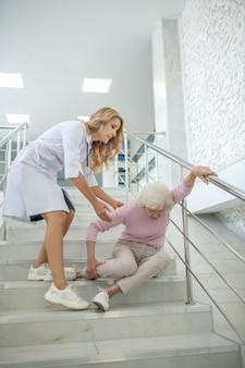 Медсестра помогает пожилой женщине, упавшей на бездомных