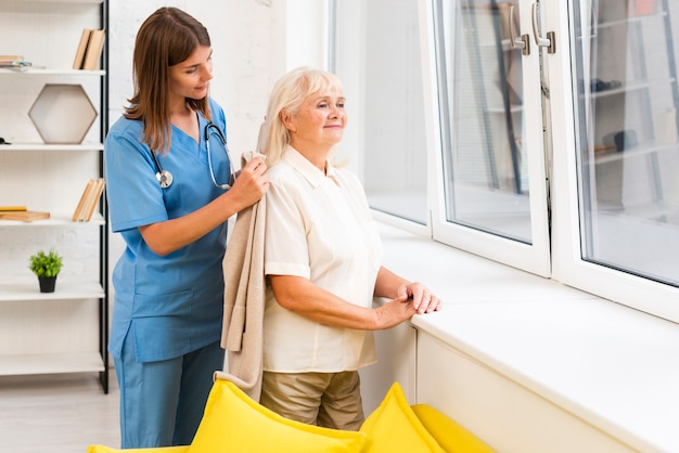 Nurse helping old woman with her coat
