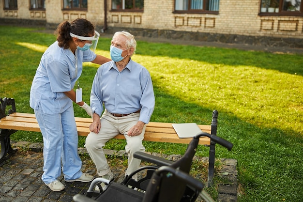 Nurse helping pensioner to stand from the bench